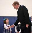 A Kindergarten student shakes the hand of the school chaplain, Fr. Jon Budke, LC, after receiving an award.
